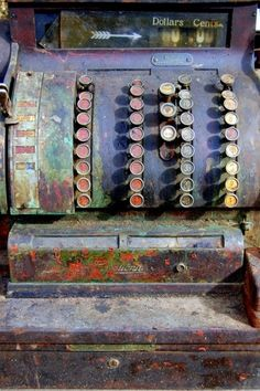 Old cash register with paint splatters.