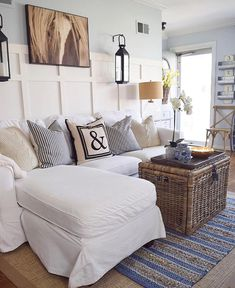rattan chest in the front of beige color sofa, and with big horse picture hanging on the wall