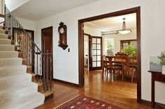 The foyer reveals a staircase and a formal dining room. White walls with wood trim. Yes.