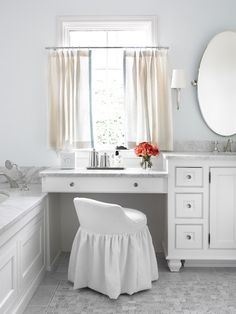 Chic bathroom with marble-top drop down make-up vanity under window covered in linen cafe curtains paired with white slipcovered vanity stool.