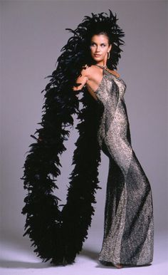 Bob Mackie - Designed for and worn by Cher. A black and silver lurex chevron knit bias cut halter style gown and black coque feather boa.
