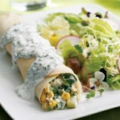 """Summer Vegetable Crêpes - Ingredients:  1/3 c reduced-fat sour cream, 1/2 c chopped fresh chives, divided, plus more for garnish, 3 tablespoons low-fat milk, 2 teaspoons lemon juice, 3/4 teaspoon salt, divided, 1 tablespoon extra-virgin olive oil, 2 c chopped zucchini, 1 1/4 c chopped green beans, 1 cup fresh corn kernels, (from 1 large ear; see Tip), 1 cup part-skim ricotta cheese, 1/2 cup shredded Monterey Jack cheese, 1/4 teaspoon freshly ground pepper, 4 9-inch """"ready-to-use"""" crêpes"""