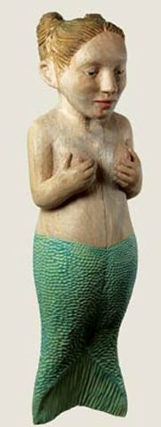Carved and painted wood sculpture of a mermaid that hangs on a wall.Claudette Schreuders
