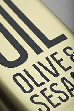 Packaging with condensed sans-serif typography and gold tin for Olive & Sesame Oil designed by Lo Siento