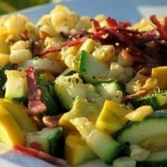 Zucchini, corn, and onions are cooked in a skillet and topped with crispy crumbled bacon and shredded Monterey Jack cheese.