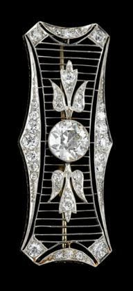 Platinum and diamond brooch art deco Petite rectangular pin displays a single Old European cut diamond, approximately 1.70 carats, surrounded by filigree diamond frame.