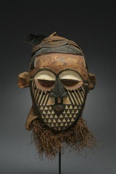 A Kuba/Kete mask Democratic Republic of Congo, of classical form, the powerful mask carved with overall geometricized features and extensive polychromy, depicting classical motifs; a fiber cap to the apex with attached plumage. height 12in (excluding attachments)