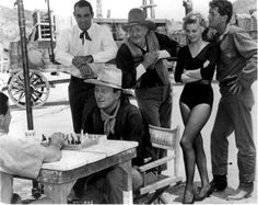1959 RIO BRAVO / John Wayne playing chess with the cast looking on