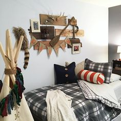 Nice wall arrangement with planks of wood, oar, brass letter, lantern, antlers, frames, and banner.