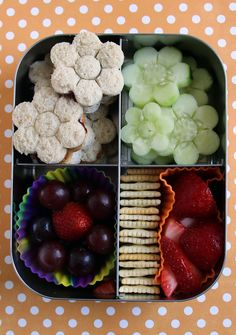 A small stamping cookie cutter makes packing tiny daisy sandwiches and cucumbers a breeze. Add a silicone cup filled with grapes arranged to look like another flower as well.