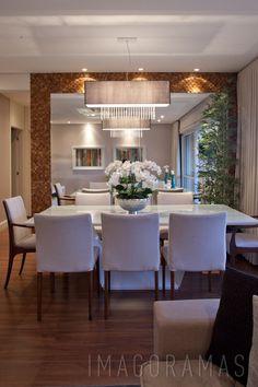 Sala de jantar com parede espelhada com moldura em pastilha de madeira