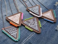 One of a kind Leather triangle pendants with brightly colored bead and stitch detail. Cut by hand using no template.