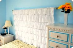 Not sure how I feel about the ruffles, but I like the idea of using a curtain rod and hanging an interesting fabric as an easy DIY headboard