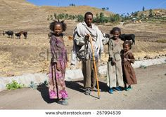 AXUM, ETHIOPIA - FEBRUARY 20, 2010: Unidentified Ethiopian man with his children watch the traffic on the roadside.  In the background there is a village.  - stock photo