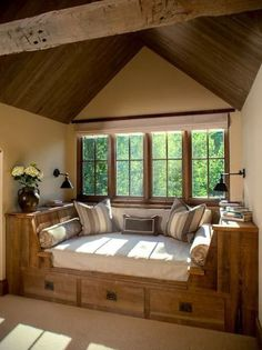 This cozy reading nook is so inspirational: a built-in lounge with its own storage beneath a wall of windows. We love all of the natural wood!
