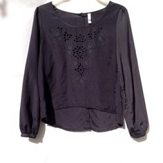 Dark Gray Blouse Beautiful dark gray blouse with flower like cut outs on front. Sleeves are cinched at the end, & it has slight puffed shoulders. The backlash buttons all the way to the top. Xhilaration Tops Blouses
