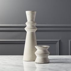 Shop avenue cement candle holders.   The shape of traditional turned wood in an unexpected material: cement.  Cool grey casts a modern light from the glow of one candle.