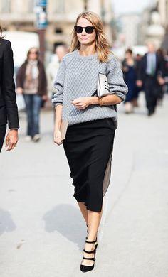 Mulher anda pelas ruas de Paris usando maxi tricot cinza mescla, saia midi preta, scarpin preto de tiras, clutch embaixo do braço e óculos escuros
