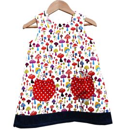 Wild Things Toadstools Dress  Wild Things Dresses is a fun new label for little girls which offers simple, versatile dresses with a funky contemporary twist.    This is a funky little cotton dress for with multi-coloured toadstool print, trimmed with indigo hem and with red polkadot pockets.100% cotton lined. Easy care wash at 30%. Smaller sizes come with lightweight elasticated indigo denim cotton knickers which fit over most nappies.