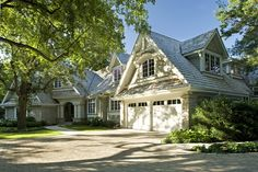 Gorgeous brick home exterior with gray shingles and Greek columns at entrance