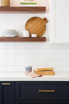 White and blue kitchen features navy blue shaker cabinets adorned aged brass pulls paired with white quartz countertops that resemble marble and a white stacked tile backsplash lined with stacked stained floating shelves.