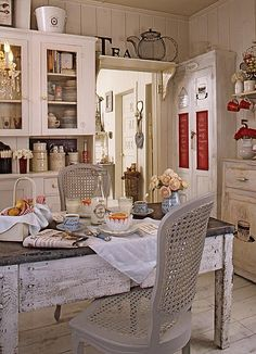 So much to see...chippy old table, crockery, shelf over door...red accents. Updated old farm house design.