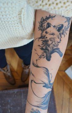 Illustration-style fox tattoo with wreath