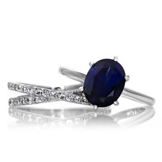 Made of sterling silver, this ring set features two slim bands, one highlighted by a large blue cubic zirconia centerpiece, the other encrusted with small white stones. These bands have a highly polis