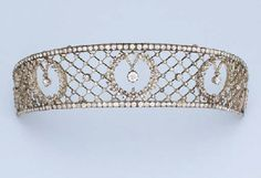 AN ANTIQUE DIAMOND TIARA   Of diamond-set trelliswork design, the three central old-cut diamond collets suspended within diamond laurel wreath to the diamond line border, mounted in silver and gold, circa 1890, 20.8 cm. inner circumference, in fitted blue leather case by Frazer & Haws, Piccadilly