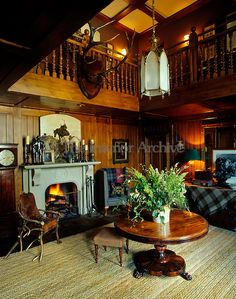 The galleried entrance hall has been designed in traditional Scottish style with tartan throws, antique hunting trophies and 19th-century furniture. Ward Denton & Christopher Gardner at Glenfeshie Lodge in Scotland.