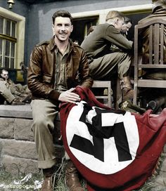 A United States Air Force officer poses with a captured Nazi flag, at the end of the war.  A colorized photo. -