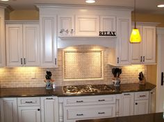 Like the cabinet design over the cooktop.  Perfect for a downdraft cooktop   Wonderful Brick Backsplash For Kitchen Decorating Ideas: Sophisticated White Cabinetry Feat Pendant Pear Lamps And Black...
