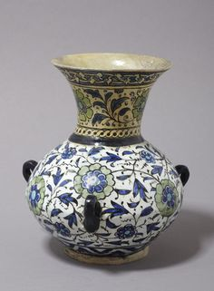 Lamp   Made in Damascus, Syria, 17th century   Materials: glazed earthenware, painted   Lamp of siliceous-glazed earthenware painted with flowers and scrolling leafy stems in green and blue. Round the top of the neck is an interlacing border, and round the base is a band of chevrons alternately reversed   VA Museum, London