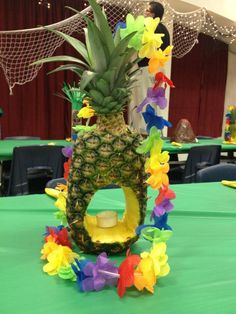 Fresh carved pineapple (from Costco) with a tea light candle for Blue & Gold Banquet luau theme. Brightly colored lei draped over for more color. #luau #decorations #partyideas