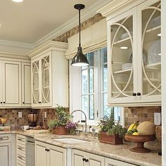 Love the backsplash and counters with the off white cabinets.
