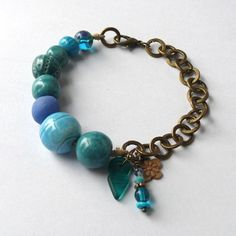 Blue ceramic, glass & bronze bracelet created with Handmade artisan beads and charms. via Etsy.