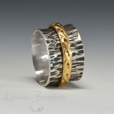 A fun, kinetic ring.  This wide band ring (½ inch) is a bit of a statement piece.  I hand-fabricated the main band from thick sterling silver, and the 14k gold-fill braided band spins freely around the wider band.  The ring is a size7¾.