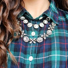 Plaid with rhinestone statement necklaces at the collar, buttoned rather high to show off the necklaces.
