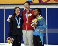 July 14 - Swimming - Women's - 100m Freestyle. Silver medal winner Natalie Coughlin (L), gold winner Chantal Van Landeghem (C) and bronze Arianna Vanderpool Wallace (R) of the Bahamas after the women's 100m Freestyle finals at the Toronto 2015 Pan American Games in Toronto, Canada July 14, 2015. AFP PHOTO / TIMOTHY A. CLARY