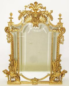 A Very Fine French Empire Style 19th Century Napoleon III Gildwood Carved Figural Mirror Frame, flanked by a pair of sitting winged sphinxes, with carved scrolls, garlands and crowned with a pierced carved Satyr's mask with foliate swags and accanthus, the top with a pair of floral urns. All gilding is the original 24 carat gold leaf. Circa: Paris, 1870