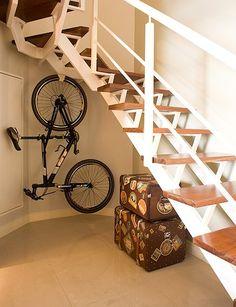 O espaço embaixo da escada é aproveitado para guardar a bicicleta, pendurada em um suporte