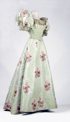 Warp printed evening gown, French, late 19th cent. Ground of pistachio silk faille jacquarded with tiny white leaves and flowers. Satin brocade worked in embroidered splashes of tiny white stylized daisies and grasses exuding from blurred oval champagne ground medallions containing polychrome sprigs. Trained skirt, boned bodice with tulle overlay and velvet band under bust.