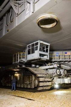 At NASA's Kennedy Space Center in Florida, a worker walks alongside the crawler-transporter as it carries space shuttle Endeavour from the Vehicle Assembly Building to Launch Pad 39A. First motion was at 4:13 a.m. EST Jan. 6. The 3.4-mile trip, known as rollout, takes about six hours. 01/06/2010 - STS-130 / Endeavour - NASA