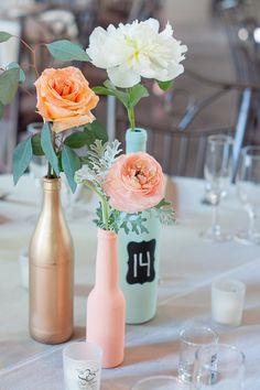 Gold, peach and teal painted glass bottles holding flowers as a centerpiece. Use chalkboard paint to add table numbers with ease!