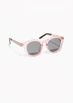 ecfa8e651c2c3 These round sunglasses have robust semi-transparent frames in light pink  and feature sleek gold-tone metal temples. Read more about our sunglasses  here.