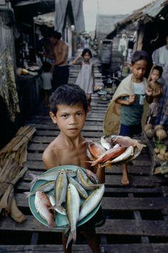 Steve McCurry. McCurry es un maestro incluyendo el entorno en sus retratos, de forma que complementen a los protagonistas y nos cuenten más de ellos. Formato V que se ajusta al pasillo, aportando profundidad y permitiendo la entrada de más personajes. PDC baja para que la atención recaiga en 1er plano, más luminoso además.
