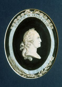 Oval, bust-length, profile portrait of George Washington, facing the viewer's right with his hair tied in 'en queue,' and wearing a crown of laurel leaves. The portrait is executed in watercolor and ink on heavy paper resembling vellum. The bust itself is in grisaille, with tonalities suggestive of plaster; the ground is of deep midnight blue watercolor. The inner bust image is mounted within a lighter-weight paper 'frame' decorated with an outer border of ribbon and garlands.