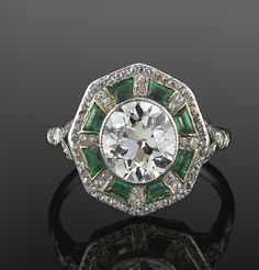2.10ct Old European Cut Diamond and Emerald Ring, circa 1915  An old European cut diamond weighing approximately 2.10 carats is surrounded by calibre emeralds and a total of approximately 1 carat of single cut diamonds set in platinum.