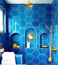 Bright blue bathroom tile and gold fixtures to feel like you're always on a luxurious vacation