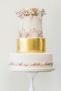 Flowers decorate a wedding cake that also features a trendy metallic tier